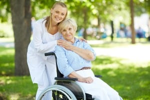 Pretty nurse and senior patient in a wheelchair looking at camer