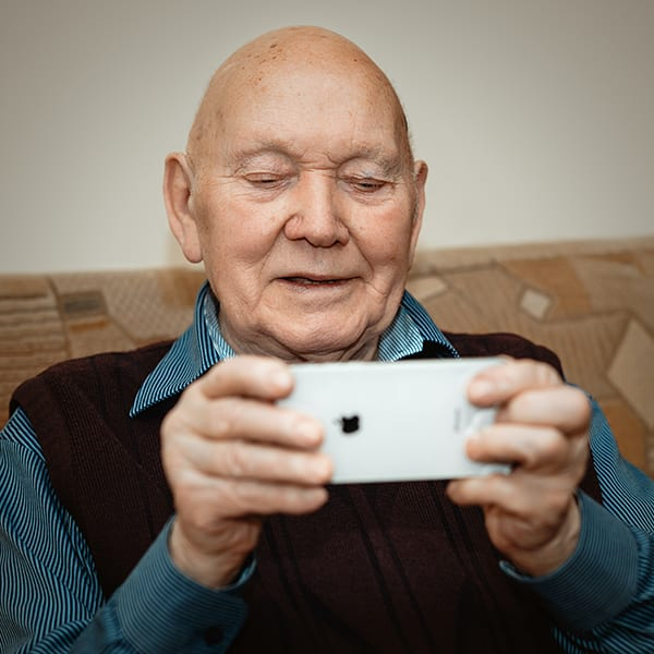 old man combatting loneliness while video-chatting family