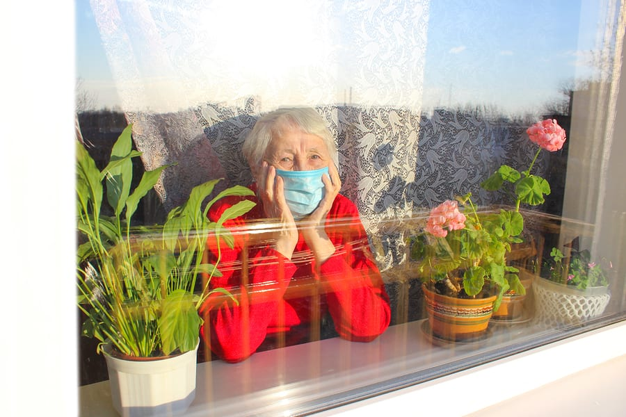 Elderly woman with mask suffering from social isolation