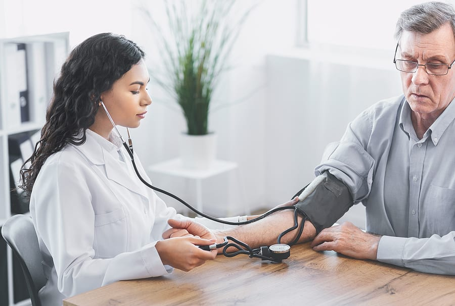 nurse checking stroke patient's blood pressure during recovery