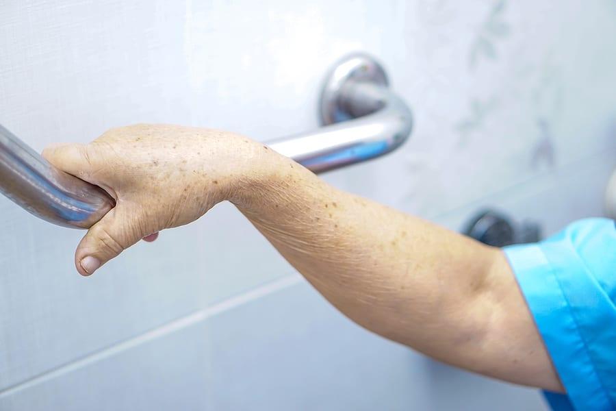 Elderly woman grabbing bar before bathing