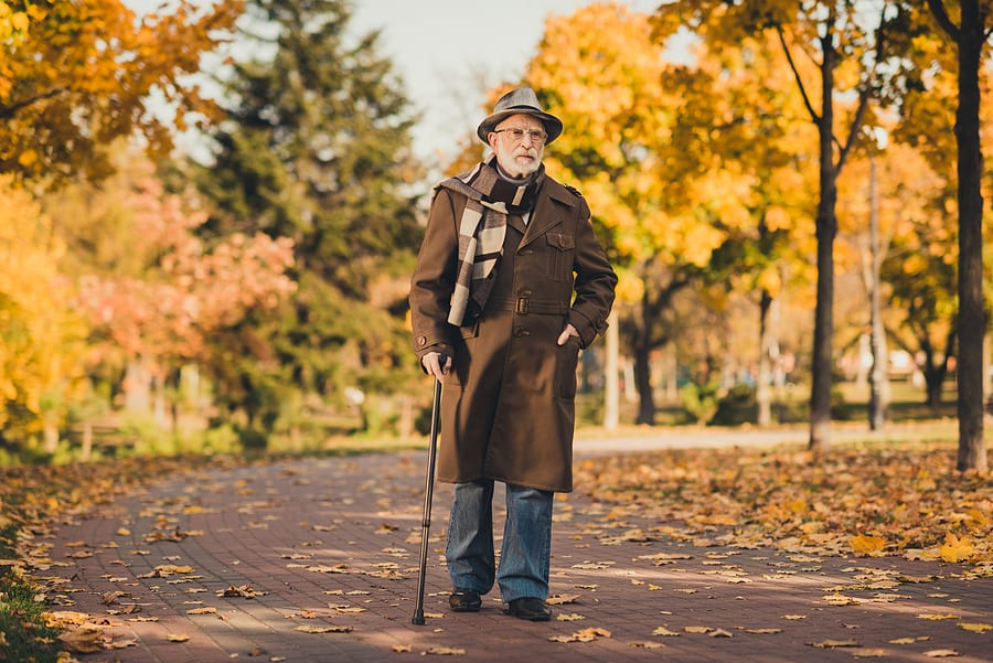 Man walking with cane to prevent fall in autumn