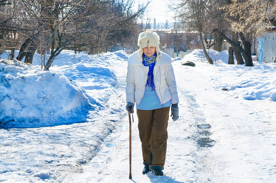 elderly woman in winter coat walking with cane after snowfall