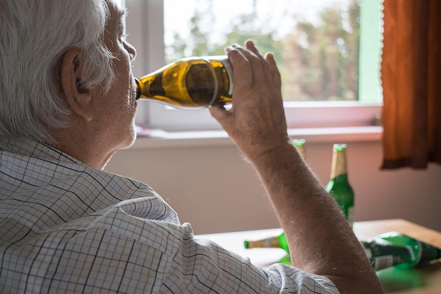 substance abuse elderly man drinking multiple bottles of beer